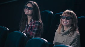 Women are watching the comedy in the cinema. The women are laughing and smiling during the watching stock footage