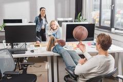 Women watching at man spinning ball. Women watching at men spinning ball at office Royalty Free Stock Image