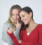Women watching phone and laughing Stock Images