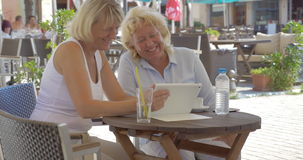 Women watching something funny on tablet PC in outdoor cafe. Two blond women sitting  with pad in street cafe. Senior friends laughing at something humorous they stock footage