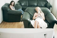 Women watching tv. Two women sitting in the living room watching tv Stock Photos