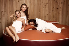 Women on a water bed. Three beautiful women in a white bathrobe and in a white towels lying on a water bed, in a wellness spa. Boudoir photography Stock Photos