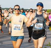 Women waving and smiling during 10K running race on boardwalk at beach stock images