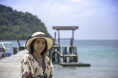 Women Wear a hat on the wooden bridge pier boat in the sea and the bright sky at Koh Kood, Trat in Thailand stock photos