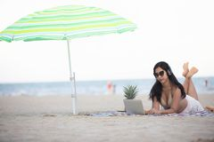 Women wearing bikinis are using laptop for work and listen to m stock photos