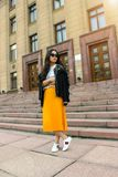 Women Wearing Black Jacket and Pleated Yellow Skirt Standing on Brown Floor Royalty Free Stock Photography