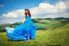 Women wearing blue long dress at sunset in Tuscany field. Royalty Free Stock Photos