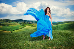 Women wearing blue long dress at sunset in Tuscany field. Royalty Free Stock Images