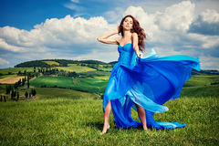 Women wearing blue long dress at sunset in Tuscany field. Stock Photography
