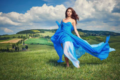 Women wearing blue long dress at sunset in Tuscany field. Stock Photo