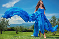 Women wearing blue long dress at sunset in Tuscany field. Stock Image