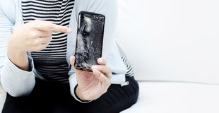 Women wearing a blue shirt holding a broken mobile phone stock images