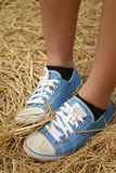Women wearing blue shoes standing on rice straw. Royalty Free Stock Photography