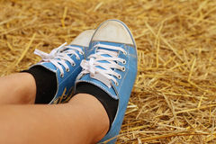 Women wearing blue shoes standing on rice straw. Royalty Free Stock Image