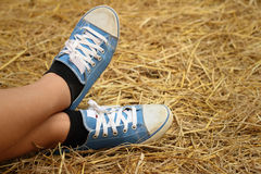 Women wearing blue shoes standing on rice straw. Stock Image