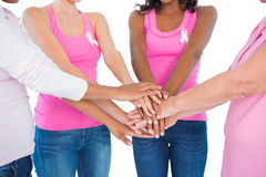 Women wearing breast cancer ribbons putting hands together. On white background Royalty Free Stock Photo