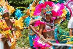 Women Wearing Costumes And Feathered Headdresses Walk In Caribbean Parade Stock Images