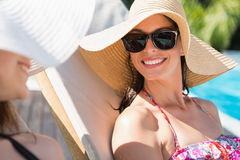 Women wearing hats by swimming pool Royalty Free Stock Image