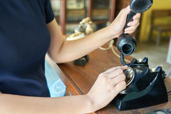 Women wearing navy dresses are picking up old phones. Hand holding telephone royalty free stock images