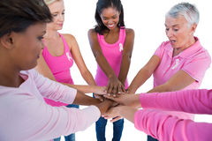 Women wearing pink and ribbons for breast cancer putting hands together Stock Photos