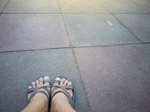 Women wearing sandals on the rubber flooring tiles. royalty free stock photos