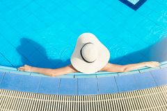 Women wearing straw hats and relax in the swimming pool. stock photography
