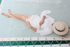 Women wearing a white dress relaxing. On net seat on the yacht with her vacation Stock Photography