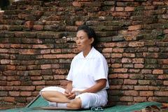 Women wearing white and sitting meditation on ancient brick wall. stock photo