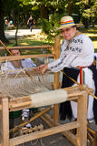 Women weaving. Demonstration of romanian traditional weaving, made it by two women wearing popular costumes, at a outdoor fair Royalty Free Stock Image