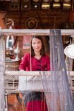 Women are weaving with ancient weaving machines. Women in thai dress are weaving with ancient weaving machines stock photos