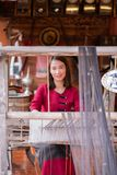 Women are weaving with ancient weaving machines. Women in thai dress are weaving with ancient weaving machines stock photo