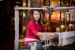 Women are weaving with ancient weaving machines. Women in thai dress are weaving with ancient weaving machines royalty free stock photo
