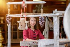 Women are weaving with ancient weaving machines. Women in thai dress are weaving with ancient weaving machines royalty free stock photography