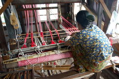 Women weaving red silk into a scarf Royalty Free Stock Photo