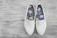 Women& x27; weiße Schuhe s und Einlegesohle von Blumen Stockbilder