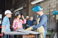 Women in welding apprenticeship lesson. In metallurgy workshop stock photos