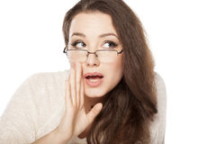 Women whispering. Beautiful young woman with eyeglasses whispering with the hand next to her mouth stock image
