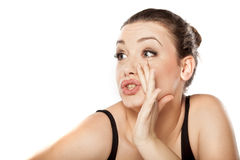 Women whispering. Young woman whispering with her hand next to her mouth stock photography