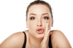 Women whispering. Young woman whispering with her hand next to her mouth stock image