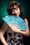 Women whit hand fan. Woman in blue corset with a hand fan on a black background with a green backlight Royalty Free Stock Photos