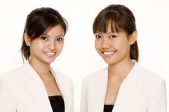 Women In White 1. Two young asian women in matching white jackets on white background Royalty Free Stock Photography