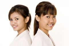 Women In White 2. Two pretty young asian women in white on white background Royalty Free Stock Image