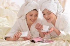 Women in white bathrobes  reading magazine Stock Photos
