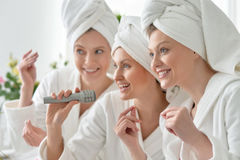 Women in white bathrobes singing with microphone Stock Photography