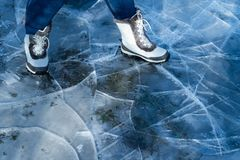 Women in white boots walking on cracked ice stock images