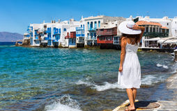 Women in white dress in front of Little Venice, Mykonos. Woman in white dress is watching the scenery of Little Venice on Mykonos island, Greece Royalty Free Stock Images