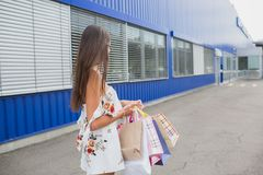 Women in white dress with shopping bags. Happy smile after buying presents. Pleasure of purchase. royalty free stock photos