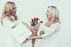 Women in White Dresses with Gift Box and Bouquet. royalty free stock photos