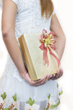 Women in white hiding a gift behind her back. Royalty Free Stock Photos