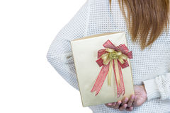 Women in white hiding a gift behind her back on white background Stock Photo